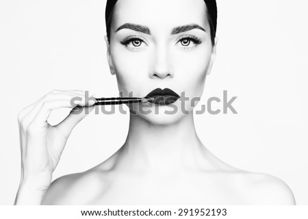 Black and white studio fashion photo of beautiful young lady applied lipstick.  Perfect face makeup - stock photo