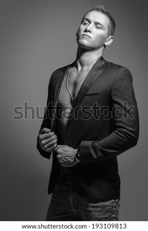 black and white studio portrait of a young, beautiful, sexy white man in a black jacket and jeans, shirtless - stock photo