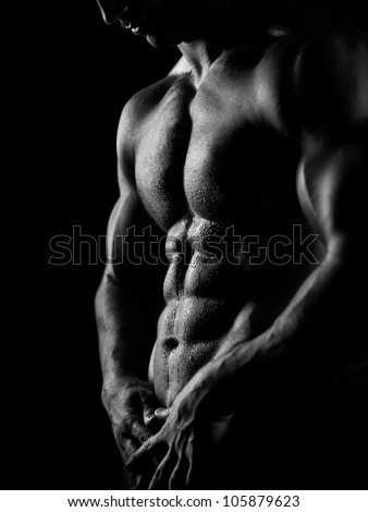 black and white studio shoot of strong athletic man on dark background - stock photo