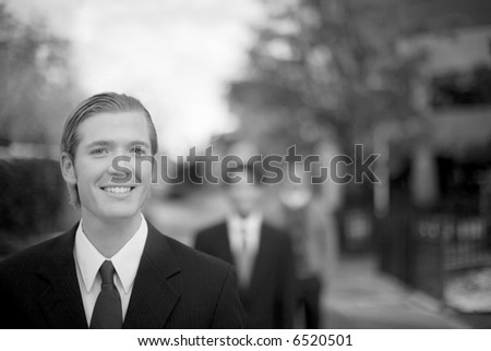 black and white three business people in staggered position smiling in front of business building structure - stock photo