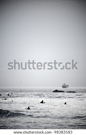 Black and white vertical photo of the surfers in the sea waiting for the waves - stock photo