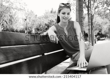 Black and white view of an attractive business woman sitting and working on her laptop computer while relaxing on a bench in a city street with trees during a sunny day, outdoors. - stock photo