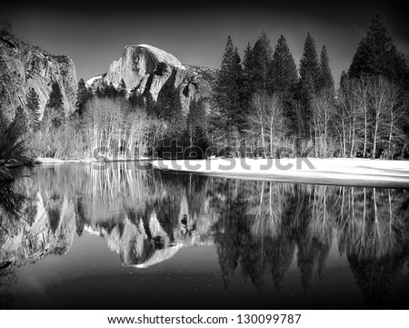 Black and white view of half dome reflected in the Merced river at Yosemite National Park - stock photo