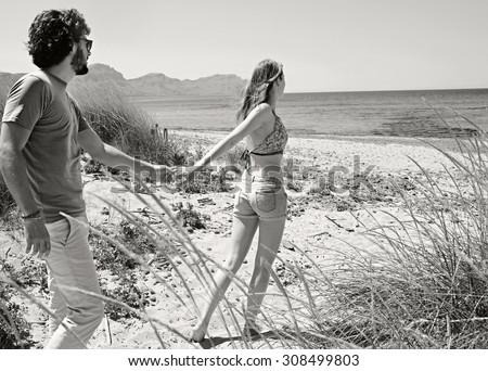 Black and white view of young tourist couple with woman taking man by the hand, walking towards the sea, enjoying a summer holiday together on a beach. Travel and lifestyle vacation, nature exterior. - stock photo