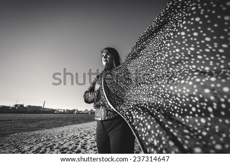 Black and white wide angle portrait of elegant woman in scarf at windy day on beach - stock photo