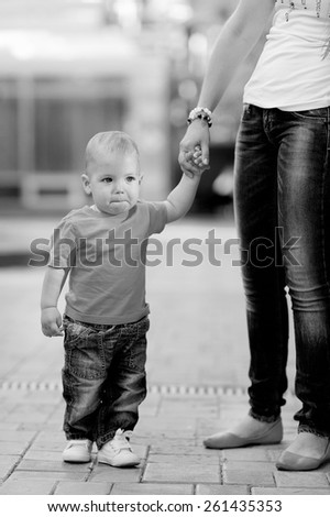 Black and white, 1 year baby, holding the hand of his mother, blond hair, jeans, mother in a white T-shirt, jeans. Against the background of trees. - stock photo