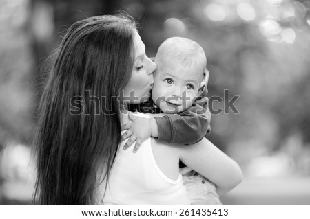 Black and white, 1 year baby in the arms of mother, blond, in a jacket, jeans, Mum beautiful brunette with straight hair, a white T-shirt. Young mother with her baby in her arms. - stock photo
