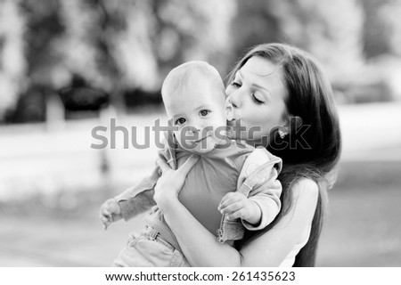 Black and white, 1 year baby in the arms of mother, blond, jeans, Mum young beautiful brunette with straight hair, a white T-shirt. Trees. Young mother with her baby in her arms. - stock photo
