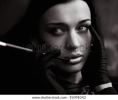 Black and white young woman in gloves smoking sigarette - stock photo