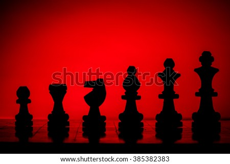 Black and yellow chess pieces on a chess board. Back light. - stock photo