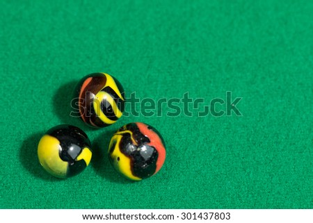 Black and Yellow Colorful Marble Balls on Green background - stock photo