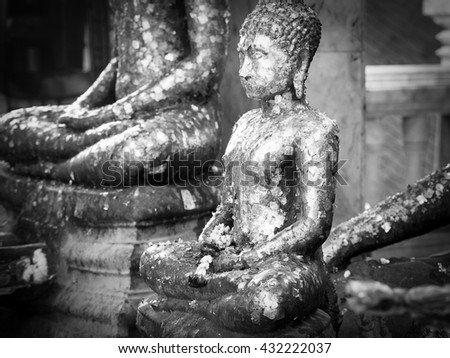 Black annd white Buddha statue with golden leaf. - stock photo