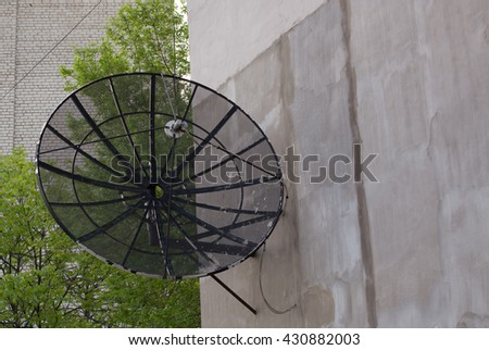 Black antenna dish on the wall of house - stock photo