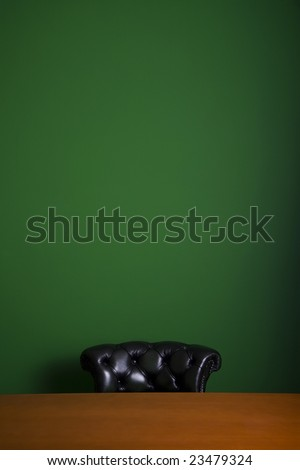black armchair behind wooden table in front of green wall - stock photo