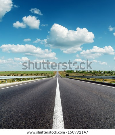 black asphalt road to horizon under deep blue cloudy sky - stock photo
