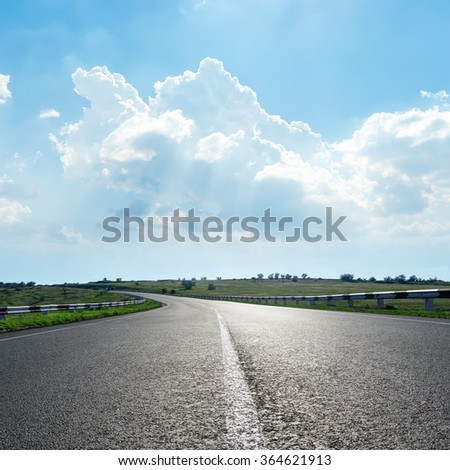 black asphalt road with white line under clouds in blue sky - stock photo