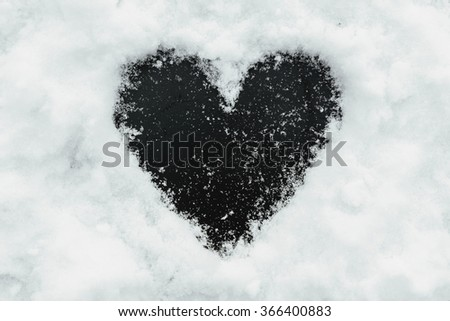 Black background shape of heart in the snow. Perfect window frame for any picture, just replace black color with your image in photo editor, by layered over it in screen mode. - stock photo