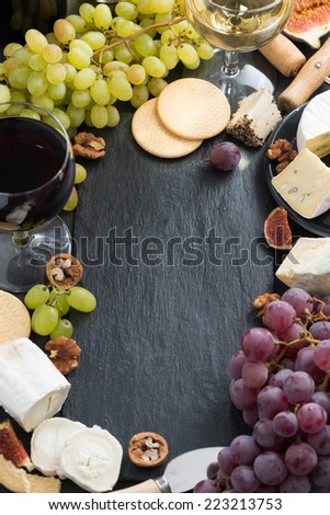 black background with cheeses, grapes, crackers and wine, top view, vertical - stock photo