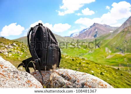 Black backpack on the stone in mountains in Kazakhstan, central Asia - stock photo