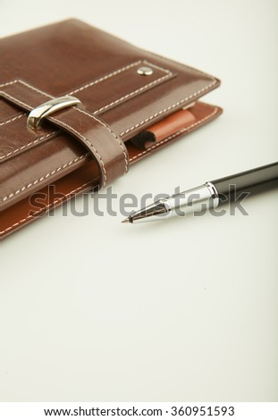 Black ballpoint pen and the leather cover diary. - stock photo