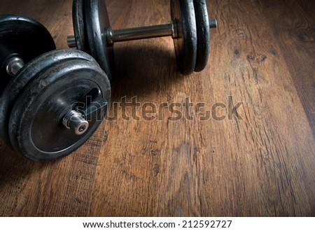 Black barbell weights on dark hardwood floor, weightlifting training concept. - stock photo