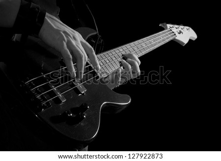 black bass-guitar in male hands over black background - stock photo