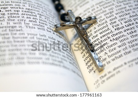 Black bead rosary in spine of open bible - stock photo