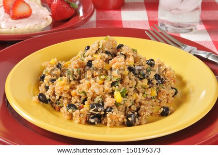 Black bean quinoa salad with an English muffin and strawberries - stock photo