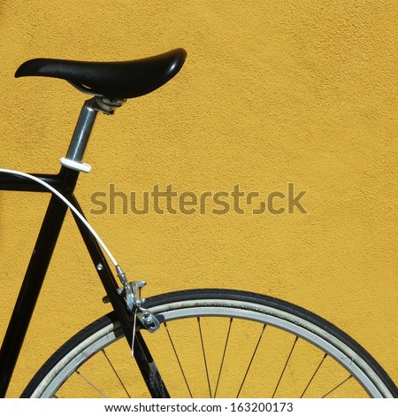 Black bicycle against a yellow wall - stock photo