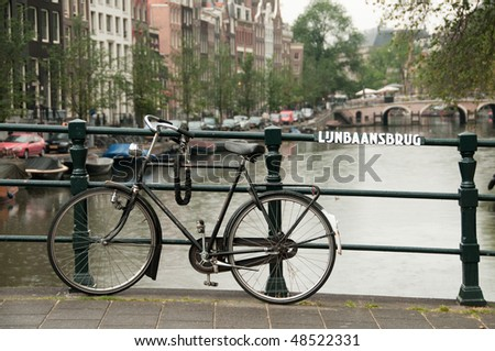 Black bike parked on Lijnbaansbrug bridge on one of the Amsterdam canals in the Netherlands - stock photo