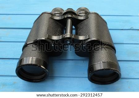 Black binoculars on blue table background - stock photo