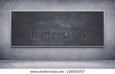 Black blackboard in concrete room - stock photo