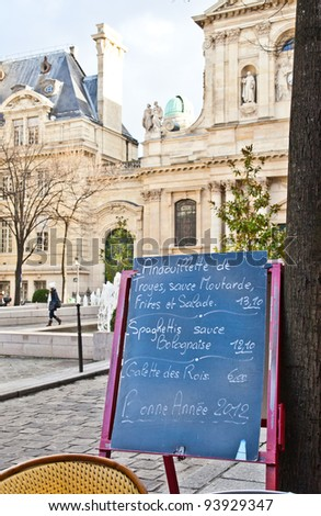 Black board with a menu restaurant in a tipical traditional square in Paris - stock photo