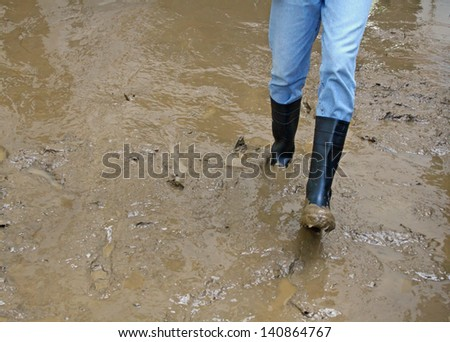 black boots in the mud of the flood after natural disaster - stock photo