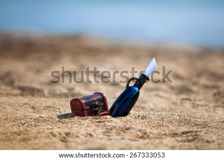 Black bottle and chest on a beach - stock photo