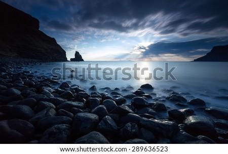 Black boulders at Talisker Bay at sunset. - stock photo
