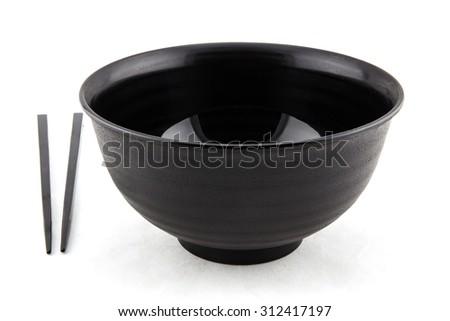 black bowl and chopsticks on white background - stock photo