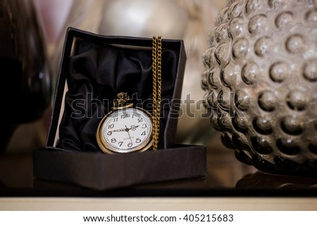 Black box with golden pocket watch on chain - stock photo