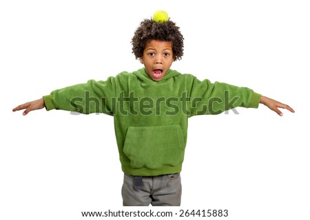 Black boy with a tennis ball on his head.  Boy plays in the relay. - stock photo