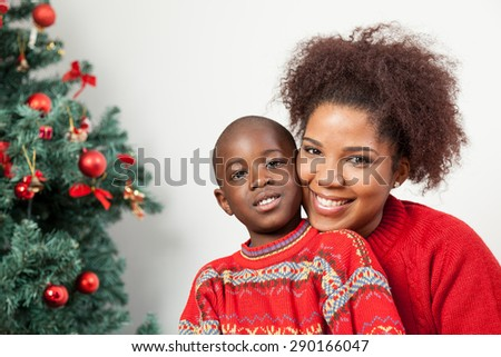 Black boy with his mother near the tree - stock photo