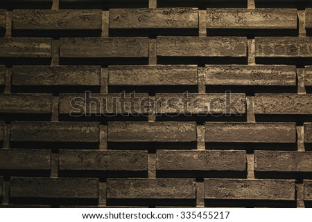 Black brick wall for background with lighting being lit on some areas - stock photo