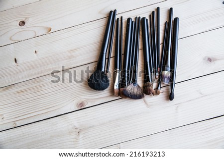 Black brush for makeup on a wooden background - stock photo