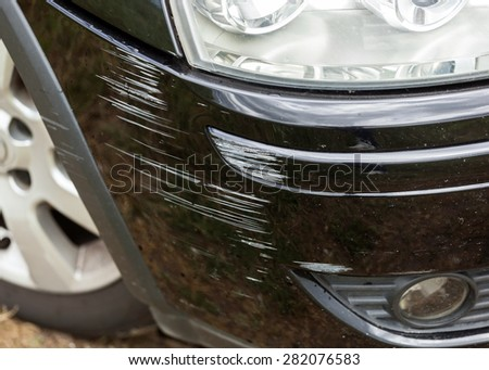 Black bumper car scratched with deep damage to the paint. - stock photo