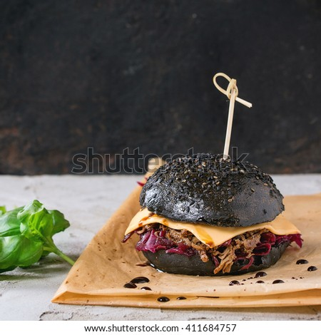 Black burger with beef stews, cheese, red cabbage and balsamic sauce served on baking paper with fresh basil over gray plastered surface with black background. Square image with selective focus - stock photo