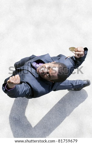 Black business man raises his fists in triumph outdoor on street. - stock photo
