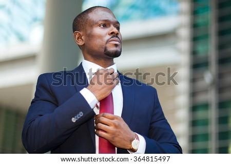 Black businessman adjusting his look - stock photo