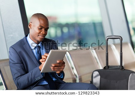 black businessman using tablet computer at airport - stock photo