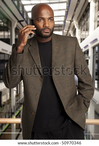 Black businessman with cell phone in office building. - stock photo