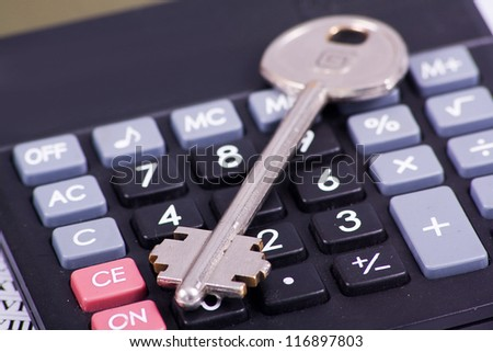 Black calculator with a key isolated on a white background - stock photo