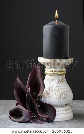 Black candle and black calla flowers (Zantedeschia). - stock photo